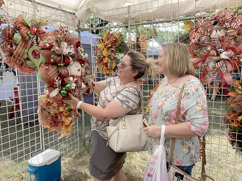 Teresa Bradford and Connie Bradford, both of Westville, Okla., look over wreaths at one of the vendor booths at the 2021 Clothesline Fair on Sunday. The fair had about 120 vendors set up on the grounds of Prairie Grove Battlefield State Park.
