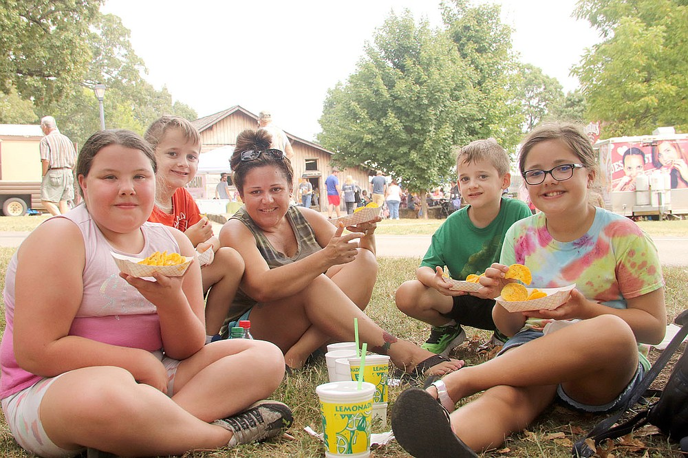 PHOTOS BY LYNN KUTTER ENTERPRISE-LEADER With temperatures in the 90s on Saturday afternoon, finding shade was important for a break from the heat. Dana Morris and her children, plus one friend, have a snack at the Clothesline Fair. Pictured are Carleigh Lyons, Michael Morris, Dana Morris, Maverick Morris and Addison Morris, all of Prairie Grove.