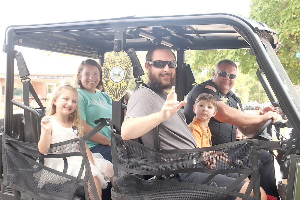 Prairie Grove police officer Tyler Franks, who was shot three times May 4 while responding to a domestic disturbance, led the 2021 Clothesline Parade with his wife, Amber, and two children. Police Chief Chris Workman is driving the vehicle.