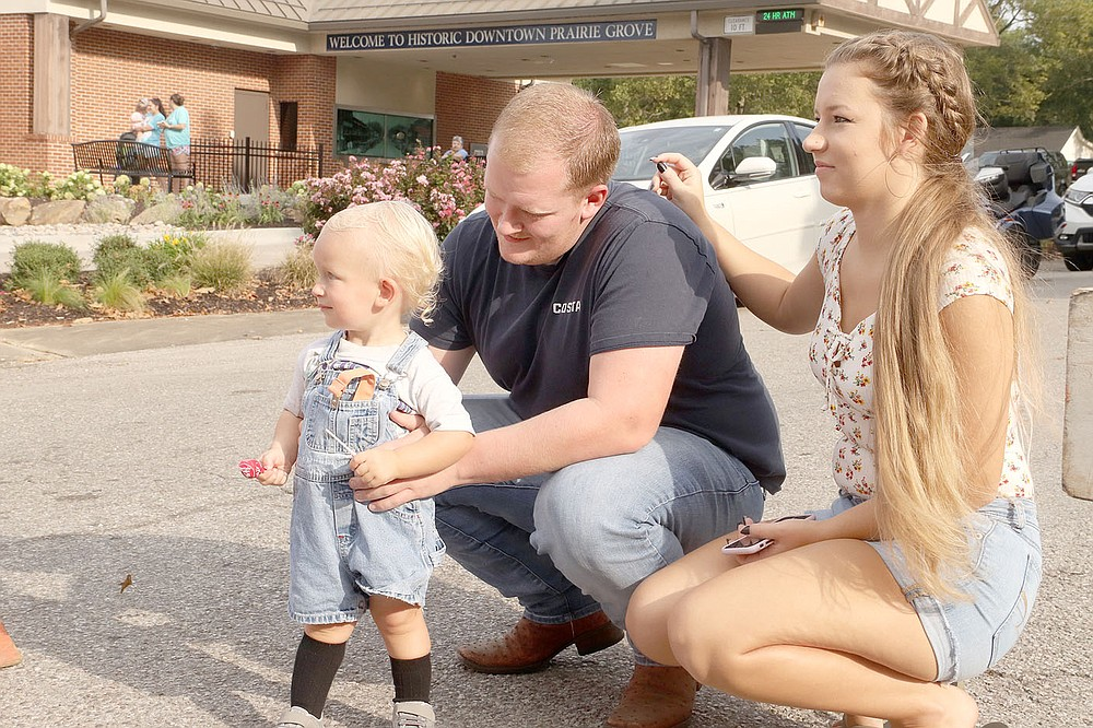 Slaiman, age 2, watches the Clothesline Parade with his parents, Cody and Heather Rex of Prairie Grove.