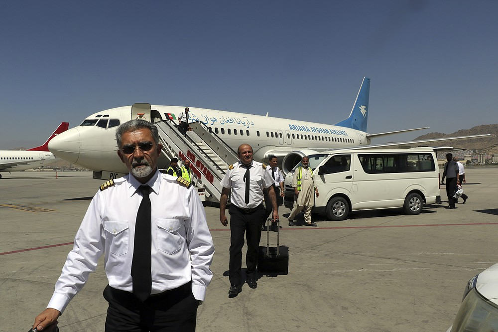 Pilots of Ariana Afghan Airlines walk on the tarmac after landing at Hamid Karzai International Airport in Kabul, Afghanistan, Sunday, Sept. 5, 2021. Some domestic flights have resumed at Kabul's airport, with the state-run Ariana Afghan Airlines operating flights to three provinces. (AP Photo/Wali Sabawoon)