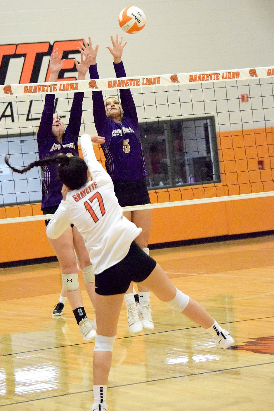 Westside Eagle Observer/MIKE ECKELS Ella Pinches (17) smashes the ball past a pair of Lady Bobcat defenders for a Lady Lion point during the third set of the Gravette-Berryville varsity volleyball match in Gravette Thursday night. The Lady Lions took the win in three straight sets over the Lady Bobcats.