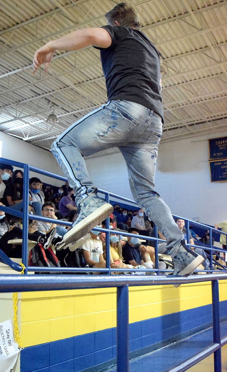 Westside Eagle Observer/MIKE ECKELS  As part of motivational dance routine, Craig Scott jumps over a rail in front of the bleachers at Peterson Gym in Decatur Sept. 8 to get the kids into the program. Scott, a surviver of the Columbine High School shooting in 1999, was in Decatur to motivate middle and high school students to be more of a positive influence on their families, friends, community and the world around them.