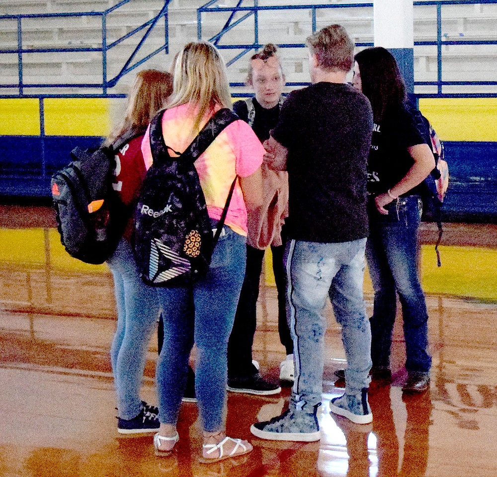 Westside Eagle Observer/MIKE ECKELS  Craig Scott (second from right) takes a moment to visit with a group of Decatur High School student after his morning assembly at Peterson Gym in Decatur Sept. 8. Scott was at Decatur High School to give students a more positive outlook on life through kindness and compassion.
