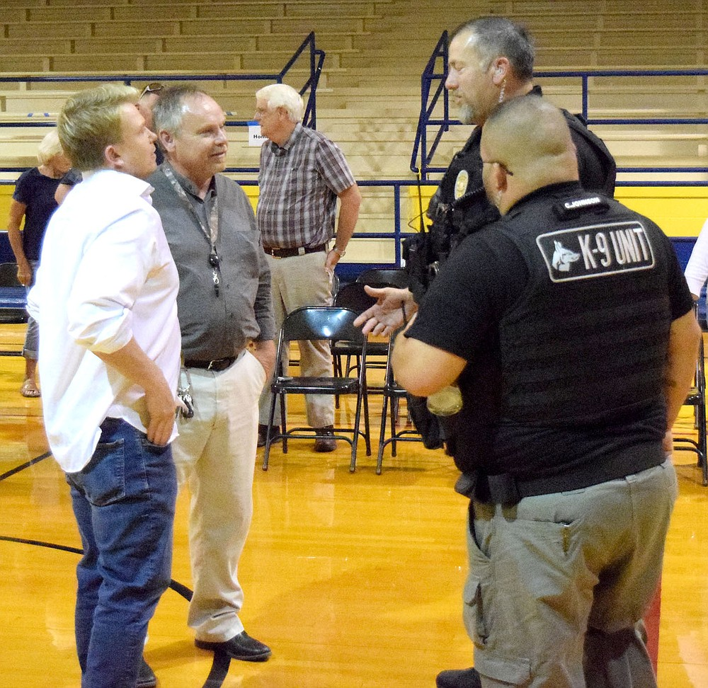 Westside Eagle Observer/MIKE ECKELS  Craig Scott (left) talks to school principal Toby Conrad, Chief Steven Grizzle and K-9 Officer Christian Johnson about some of the events that occurred during the April 20, 1999 shooting at his high school in Littleton, Colorado. Scott survive the event but his sister Rachel Joy was the first of 15 victims to lose their life in that tragic event.