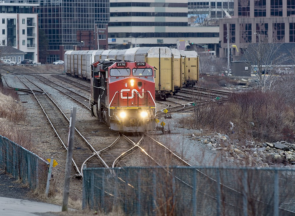 FILE - In this March 29, 2018 file photo, a Canadian National Rail locomotive moves through the rail yard in Dartmouth, Nova Scotia. Kansas City Southern is in talks with Canadian Pacific, Saturday, Sept. 4, 2021, to determine whether its $31 billion bid is the best offer on the table after regulators rejected a key part of Canadian National's $33.6 billion offer last week.   (Andrew Vaughan/The Canadian Press via AP)