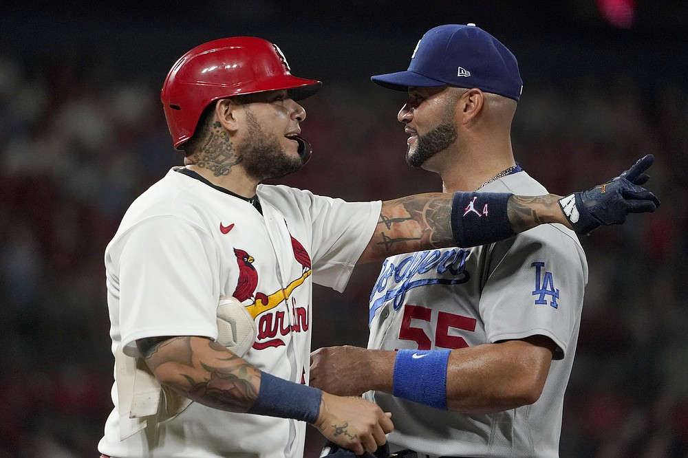 St. Louis Cardinals' Yadier Molina, left, jokes with Los Angeles Dodgers first baseman Albert Pujols after hitting a single during the third inning of a baseball game Tuesday, Sept. 7, 2021, in St. Louis. (AP Photo/Jeff Roberson)