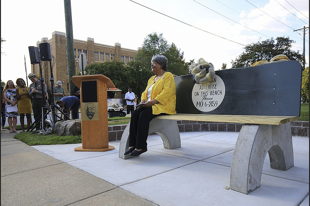 Elizabeth Eckford takes a seat Sept. 4, 2018, on a bench dedicated in her honor across from Little Rock Central High School. The bench is a replica of the public city bus bench where Eckford sought shelter in 1957 from the mob that was protesting the school's desegregation. (Democrat-Gazette file photo)