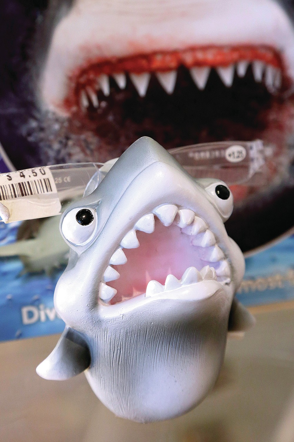 FILE— In this July 2, 2014 file photo, an eye glass holder in the shape of a shark rests on a shelf in a souvenir shop in Chatham, Mass. Cape Cod is slowly embracing its shark reputation, three summers after the popular vacation destination saw its first great white shark attacks in generations. A growing group businesses are cashing in on the shark trend with retail offerings to tourists and charter boat operators giving visitors a chance to see the marine predators up close. (AP Photo/Steven Senne, File)