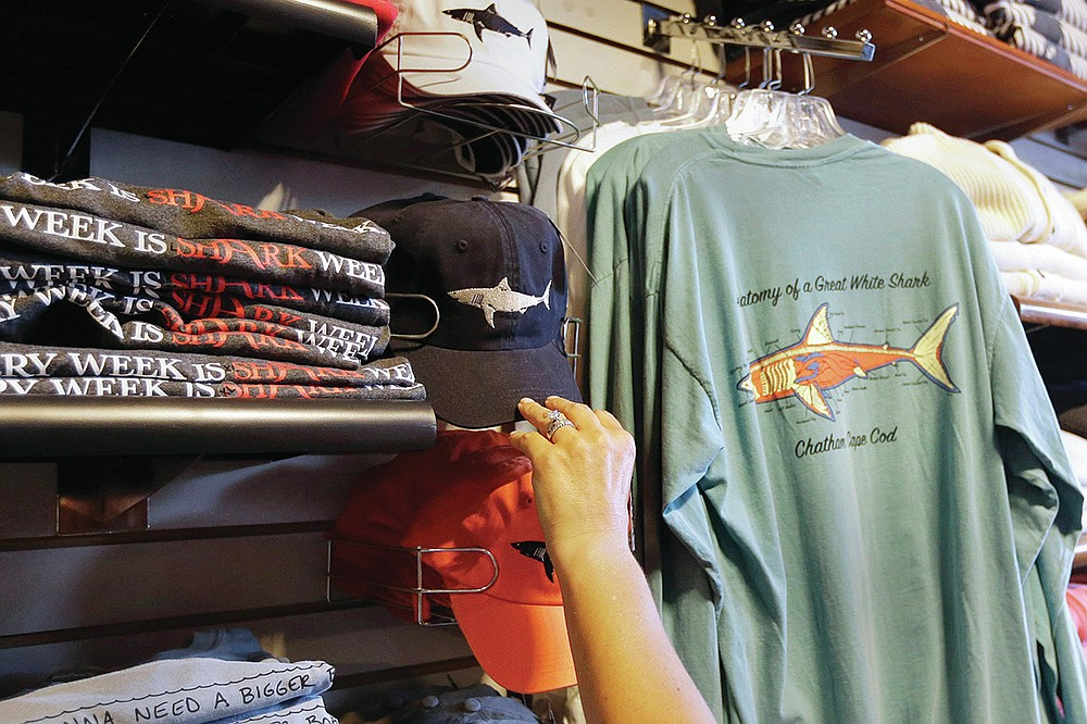 FILE— In this July 2, 2014 photo, a customer examines shark-themed clothing at a store in Chatham, Mass. Cape Cod is slowly embracing its shark reputation, three summers after the popular vacation destination saw its first great white shark attacks in generations. A growing group businesses are cashing in on the shark trend with retail offerings to tourists and charter boat operators giving visitors a chance to see the marine predators up close. (AP Photo/Steven Senne, File)