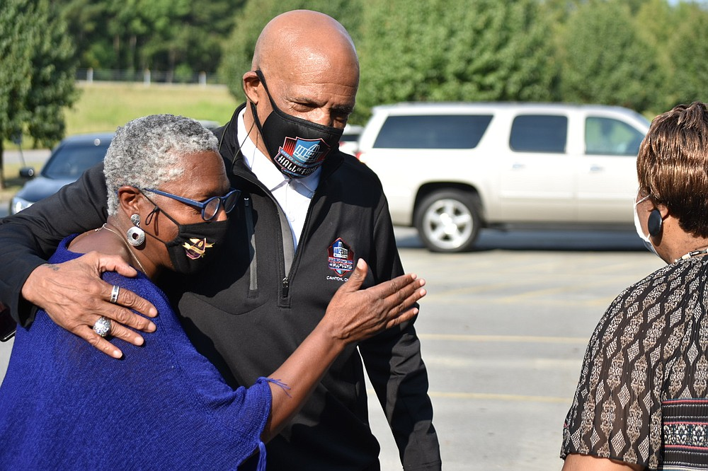 Joyce Campbell, a program outreach coordinator for the city of Pine Bluff, hugs Pro Football Hall of Famer Drew Pearson as Dorothy Oliver, a coordinator for the city's Advancing Health Literacy Program, looks on. (Pine Bluff Commercial/I.C. Murrell)