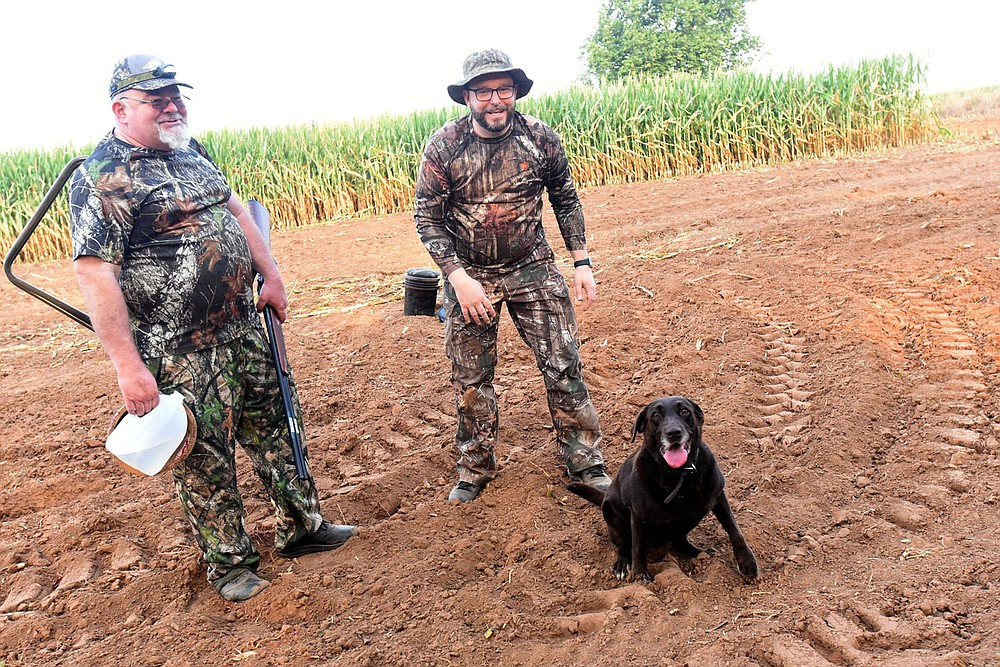 Russell Pardue (left) of Tulsa, Okla. and Craig Pardue of Fayetteville wrap up their opening-morning dove hunt on Sept. 4 2021 near Prairie Grove with their retriever, Brooke.  (NWA Democrat-Gazette/Flip Putthoff?