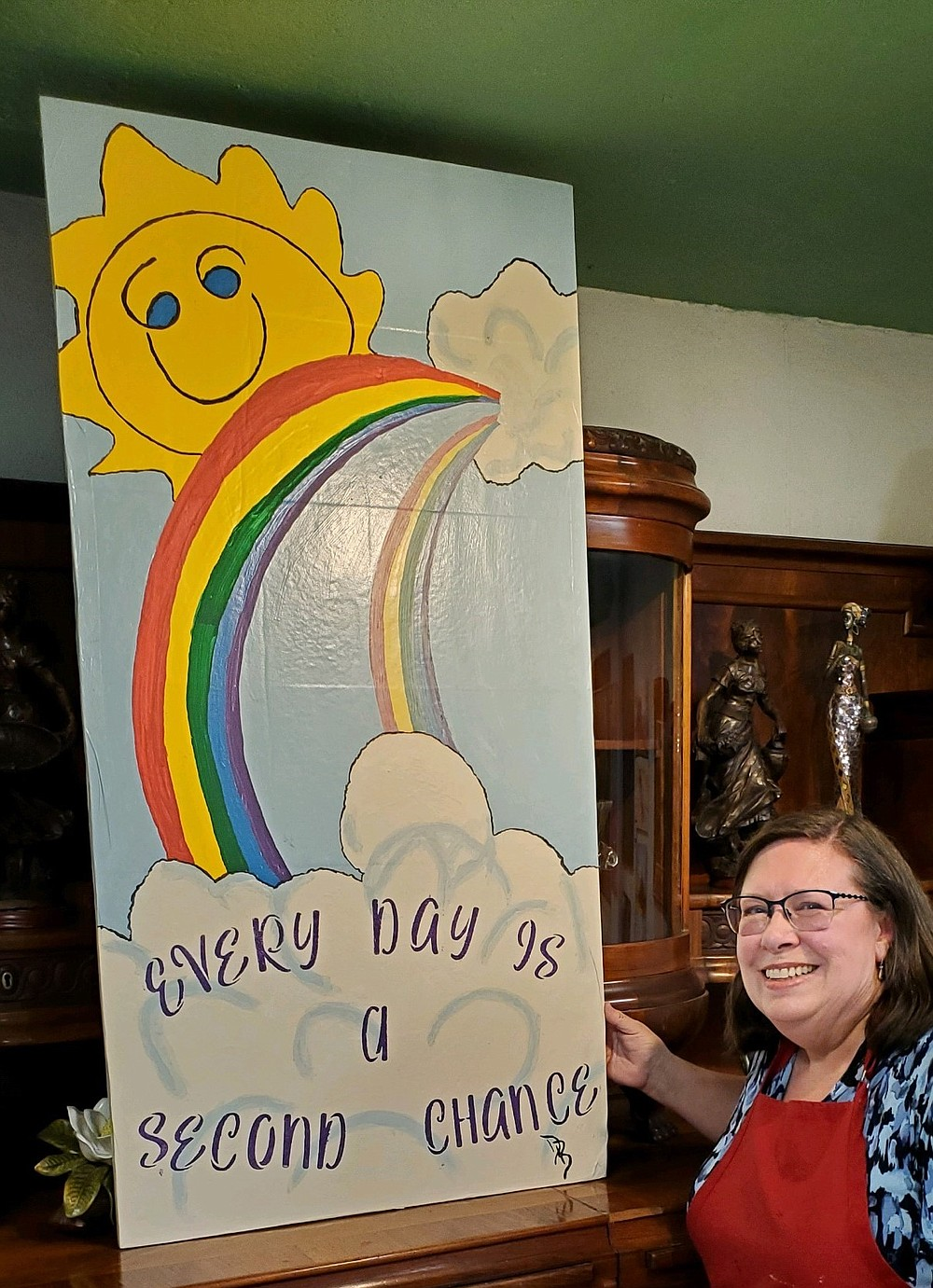Submitted photo Denise Bolster, a local breast cancer survivor, stands near an inspirational painting with a creed she believes about life, Every day is a second chance.