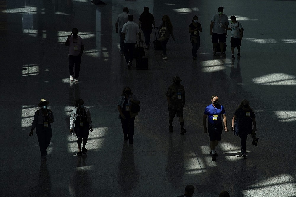 People walk through the Las Vegas Convention Center on final day of the the ASD Market Week convention Wednesday, Aug. 25, 2021, in Las Vegas. In pre-COVID times, business events like conferences and trade shows routinely attracted more than 1 billion participants and $1 trillion in direct spending each year. The pandemic brought those gatherings to a sudden halt, and now in-person meetings are on the rebound from Las Vegas to Beijing. (AP Photo/John Locher)