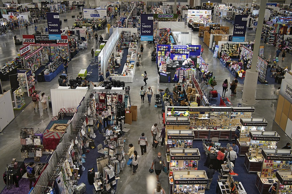 People walk through the convention floor at the ASD Market Week convention Wednesday, Aug. 25, 2021, in Las Vegas. In pre-COVID times, business events like conferences and trade shows routinely attracted more than 1 billion participants and $1 trillion in direct spending each year. The pandemic brought those gatherings to a sudden halt, and now in-person meetings are on the rebound from Las Vegas to Beijing. (AP Photo/John Locher)