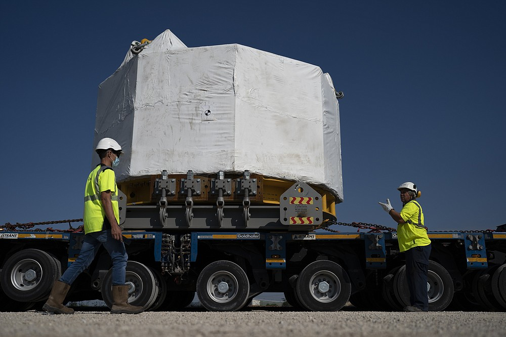 Workers secure a central solenoid magnet for the ITER project as it departs from Berre-l'Etang in southern France, Monday, Sept. 6, 2021. The first part of a massive magnet so strong its American manufacturer claims it can lift an aircraft carrier arrived Thursday, Sept. 9, 2021 at a high-security site in southern France, where scientists hope it will help them build a 'sun on earth.' Almost 60-feet tall and 14 feet in diameter when fully assembled, the magnet is a crucial component of the International Thermonuclear Experimental Reactor, or ITER, a 35-nation effort to develop an abundant and safe source of nuclear energy for future generations.(AP Photo/Daniel Cole)