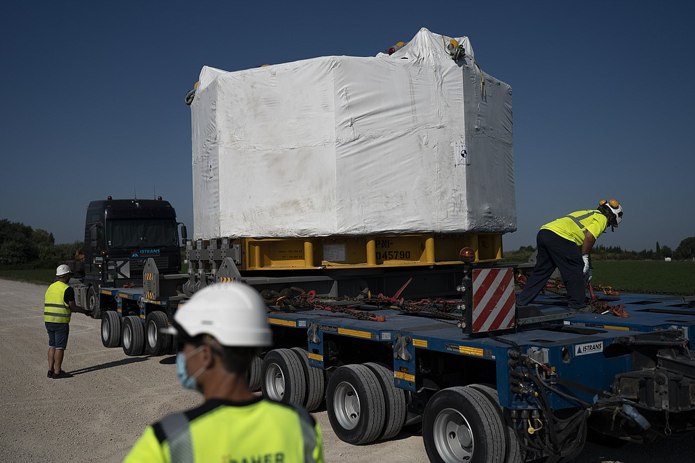 Workers secure a central solenoid magnet for the ITER project as it departs from Berre-l'Etang in southern France, Monday, Sept. 6, 2021. The first part of a massive magnet so strong its American manufacturer claims it can lift an aircraft carrier arrived Thursday, Sept. 9, 2021 at a high-security site in southern France, where scientists hope it will help them build a 'sun on earth.' Almost 60-feet tall and 14 feet in diameter when fully assembled, the magnet is a crucial component of the International Thermonuclear Experimental Reactor, or ITER, a 35-nation effort to develop an abundant and safe source of nuclear energy for future generations. (AP Photo/Daniel Cole)