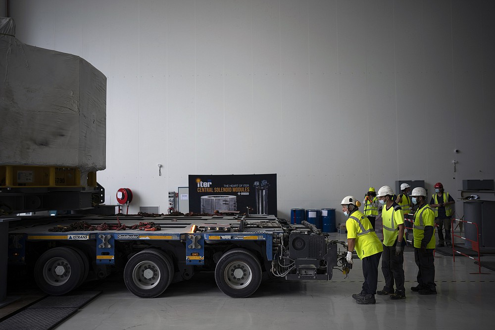 Workers receive a central solinoid magnet for the ITER project in Saint-Paul-Lez-Durance, France, Thursday, Sept. 9, 2021. Scientists at the International Thermonuclear Experimental Reactor in southern France took delivery of the first part of a massive magnet so strong its American manufacturer claims it can lift an aircraft carrier. (AP Photo/Daniel Cole)