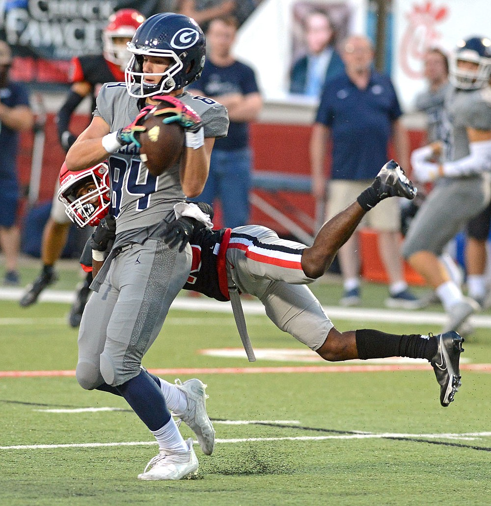 Greenwood's Luke Brewer (84) catches a ball, thrown by quarterback Hunter Houston, as he is hit by Fort Smith Northside's Zavian Zeffer (10) on Friday, Sept. 10, 2021 in Fort Smith. (Special to NWA Democrat Gazette/Brian Sanderford)