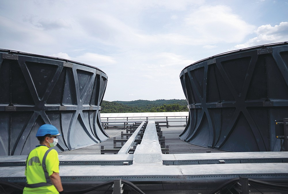 A worker surveys the cooling tower area of the ITER machine in Saint-Paul-Lez-Durance, France, Thursday, Sept. 9, 2021. Scientists at the International Thermonuclear Experimental Reactor in southern France took delivery of the first part of a massive magnet so strong its American manufacturer claims it can lift an aircraft carrier. (AP Photo/Daniel Cole)