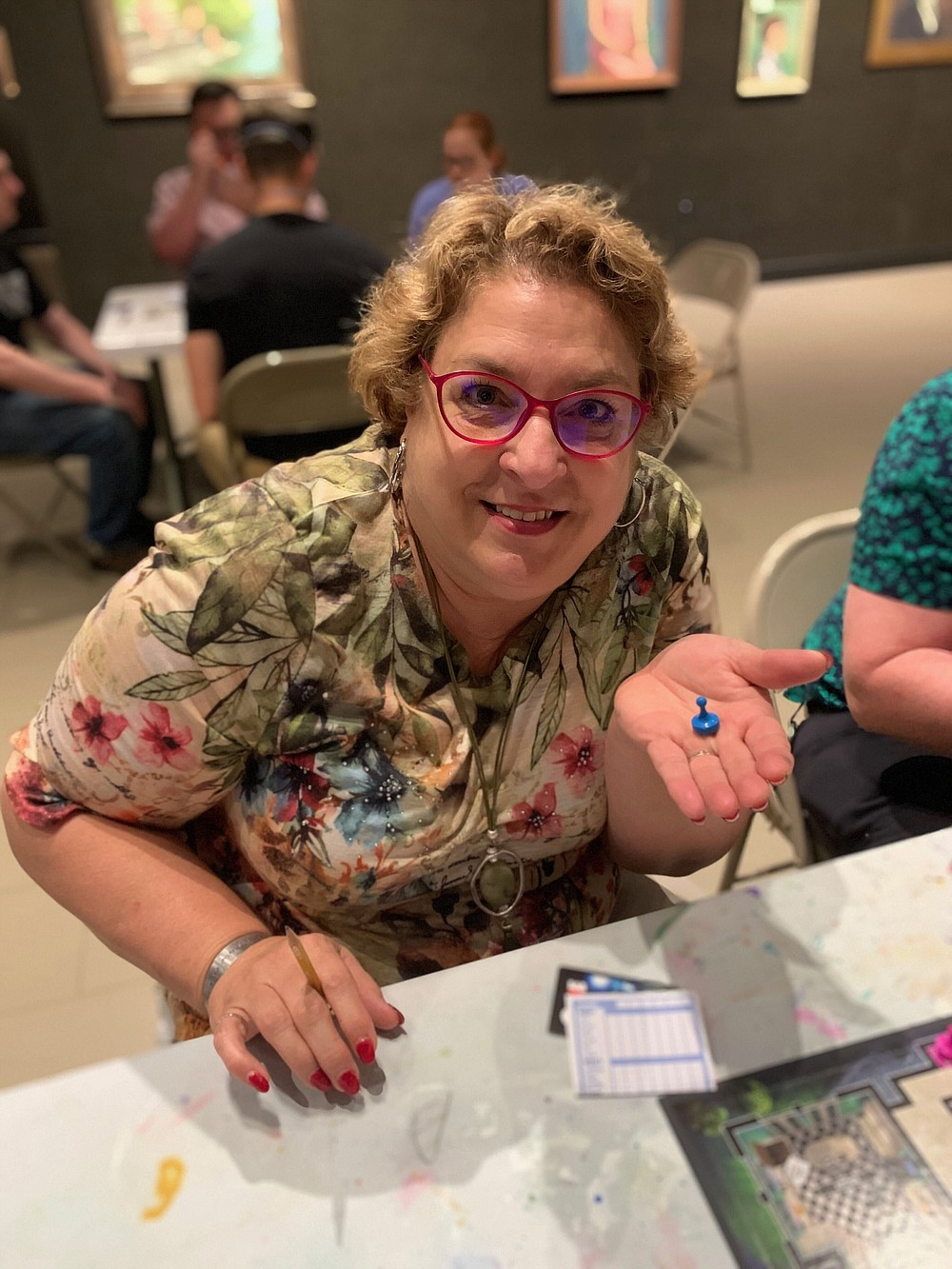 """Traci Stevenson, who will play Mrs. Peacock in the South Arkansas Arts Center's upcoming production of """"Clue: On Stage"""" enjoys a game of Clue in the SAAC art gallery. (Contributed)"""