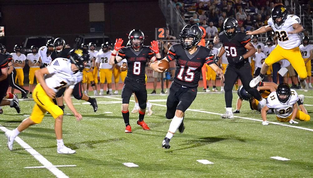 ANNETTE BEARD PEA RIDGE TIMES/Prairie Grove Tigers converge on the Blackhawk quarterback Gavin Dixon (No. 15) Friday night in Blackhawk Stadium.