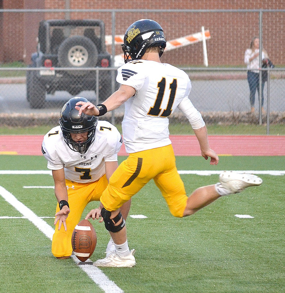 ANNETTE BEARD PEA RIDGE TIMES/Prairie Grove junior Payton Higgins (Tiger No. 11) kicks for the extra-point out of the hold of Camden Patterson (No. 7) after a Tiger touchdown Friday, Sept. 10, 2021.