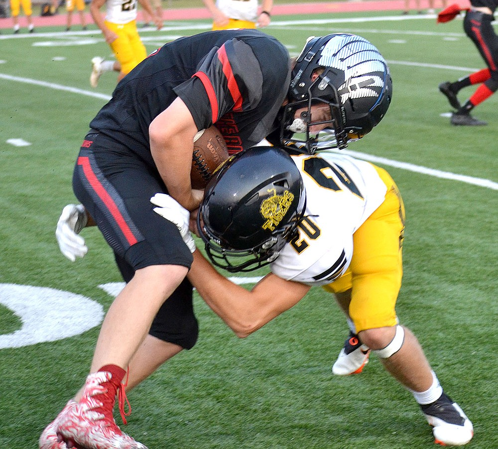 ANNETTE BEARD PEA RIDGE TIMES/Prairie Grove senior Colin Faulk (Tiger No. 20) tackles Blackhawk sophomore Bowen Phillips (No. 41) Friday, Sept. 10. Prairie Grove held the Blackhawks scoreless in the second and third quarters while posting a 41-28 nonconference football win.