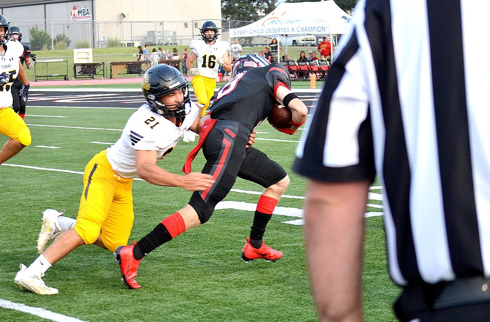 ANNETTE BEARD PEA RIDGE TIMES/Prairie Grove junior Rhett Marrell (Tigers No. 21) tries to tackle Blackhawk senior Trevor Blair (No. 8) on Friday, Sept. 10, 2021. The Tigers emerged victorious on the road by a 41-28 score.