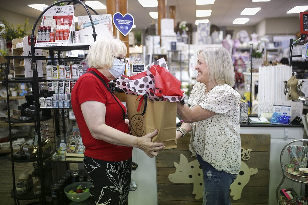 Dotted Pig owner Sherry Puttkammer (right) hands goods to Meza Harris of Rogers  Friday at the Dotted Pig in Rogers. The city of Rogers' sales tax topped $2 million and for the first time was the highest among the four large cities in Northwest Arkansas. Check out nwaonline.com/210912Daily/ for today's photo gallery.  (NWA Democrat-Gazette/Charlie Kaijo)
