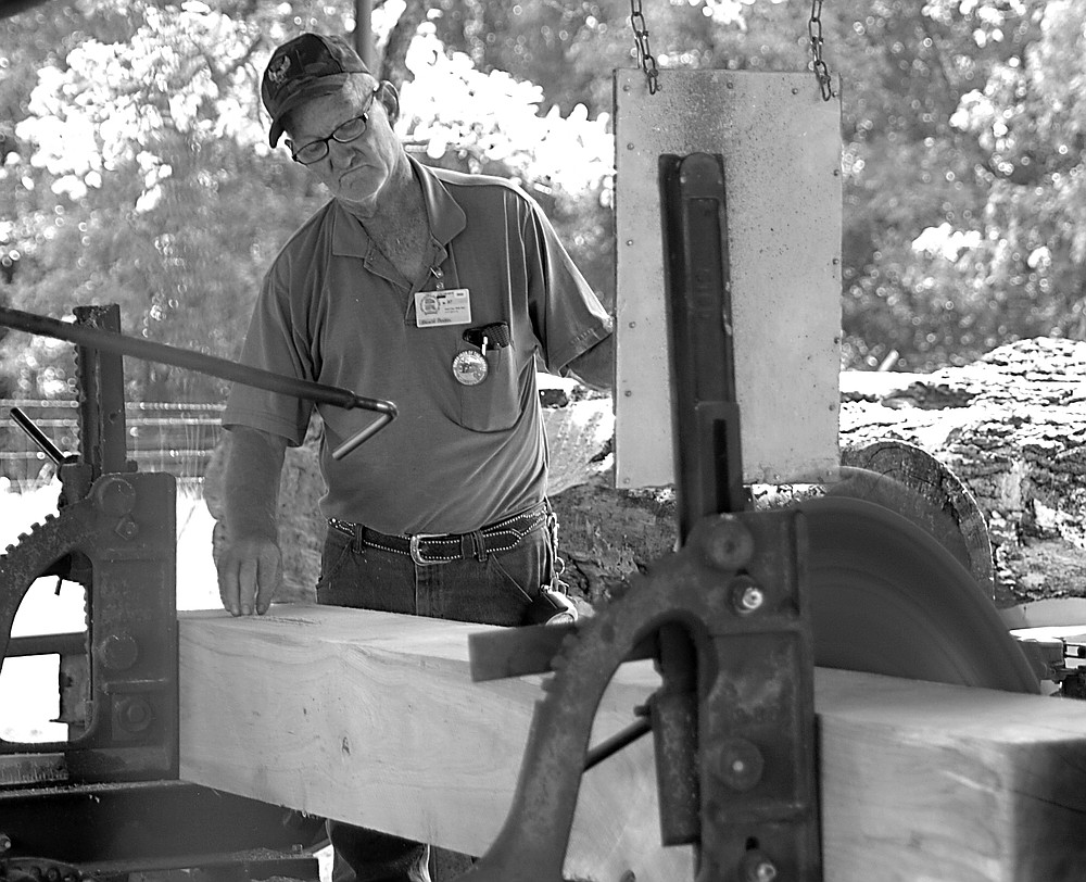 Westside Eagle Observer/RANDY MOLL Harold Bowen, of Huntsville, demonstrates use of the sawmill at the Tired Iron of the Ozarks fall show on Saturday, Sept. 11, 2021.