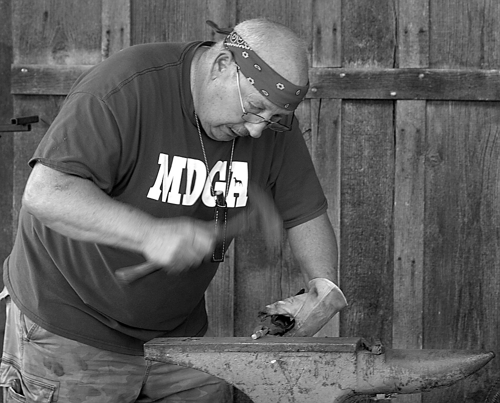 Westside Eagle Observer/RANDY MOLL Ray Kirk of Keys, Okla., hammers a heated piece of iron into shape at the Tired Iron of the Ozarks fall show on Saturday, Sept. 11, 2021. Kirk is part of the American Bladesmith Society.