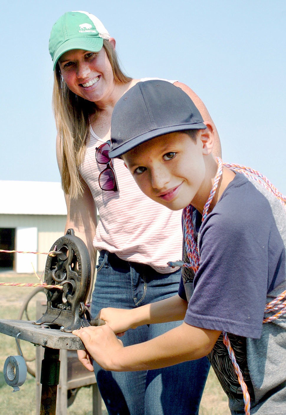Westside Eagle Observer/RANDY MOLL Derriek Arce, 9, and his mother Ashley make a rope from strands of baling twine at the Tired Iron of the Ozarks fall show on Saturday, Sept. 11, 2021.