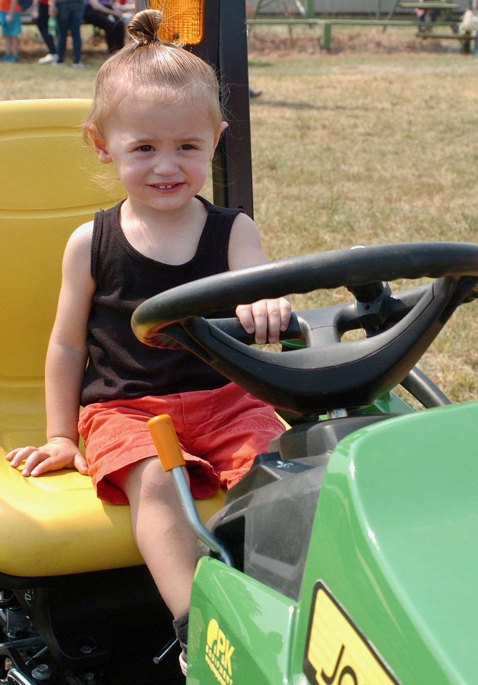 Westside Eagle Observer/RANDY MOLL Emerson Lago, 20 months, sits in the seat of a John Deere mower at the fall show of the Tired Iron of the Ozarks on Saturday, Sept. 11, 2021.