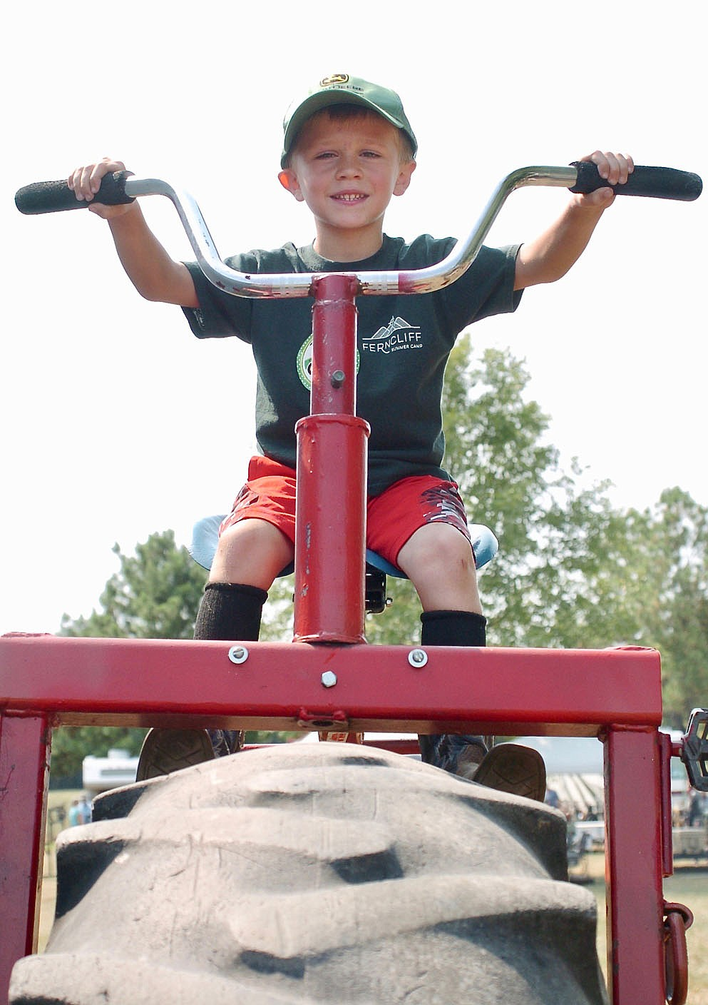 Westside Eagle Observer/RANDY MOLL Paxton Smith, 5, sits atop a tractor-size tricycle at the Tired Iron of the Ozarks fall show in Gentry on Saturday, Sept. 11, 2021.