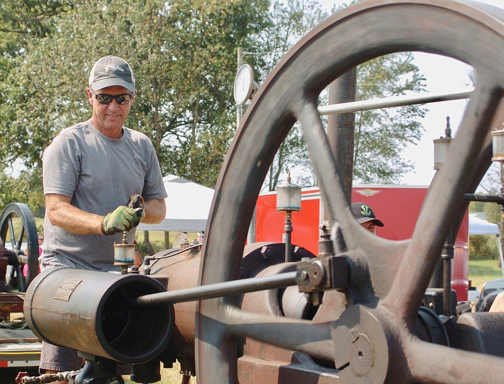 Westside Eagle Observer/RANDY MOLL Mark Dixon of Siloam Springs makes some adjustments on his 1921 Reid oilfield engine at the Tired Iron of the Ozarks antique tractor and engine show on Saturday, Sept. 11, 2021.