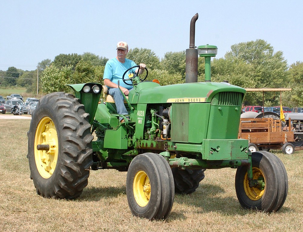 Westside Eagle Observer/RANDY MOLL Frank Leeman drives a John Deere tractor belonging to Russell Leeman in the Parade of Power held at noon Saturday during the Tired Iron of the Ozarks fall show in Gentry.