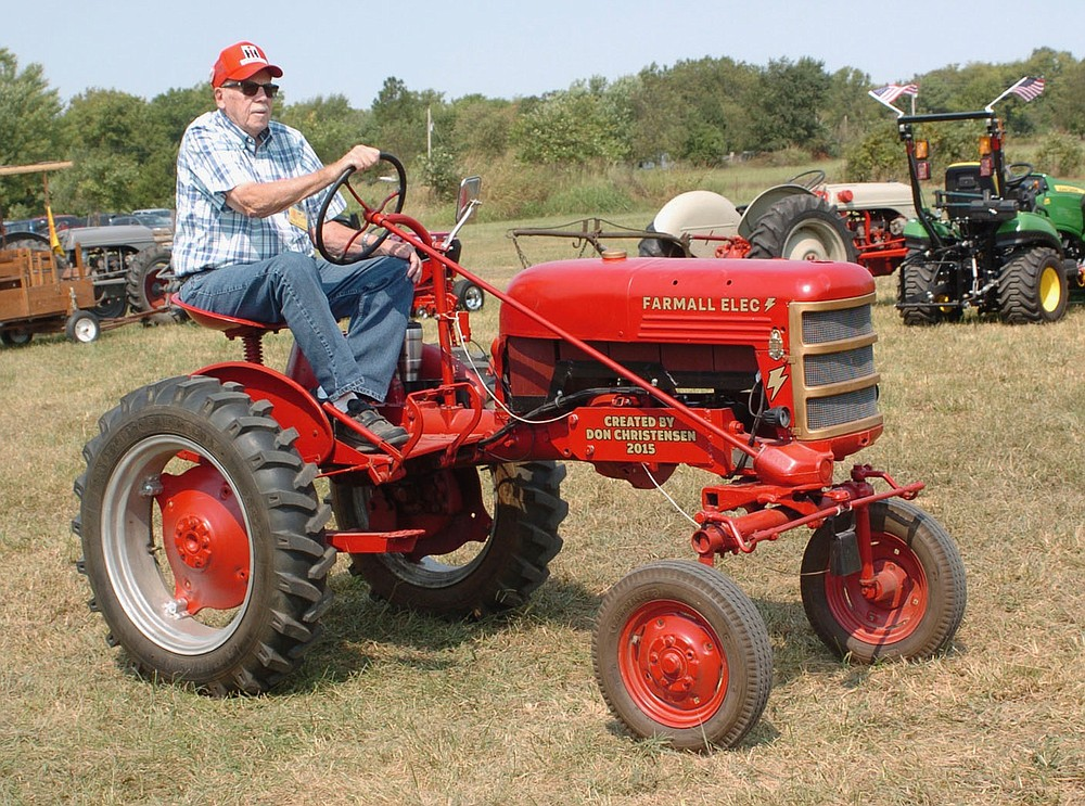 Westside Eagle Observer/RANDY MOLL Don Christensen drives his Farmall electric tractor during the Parade of Power held Saturday at noon at the Tired Iron of the Ozarks fall show in Gentry.