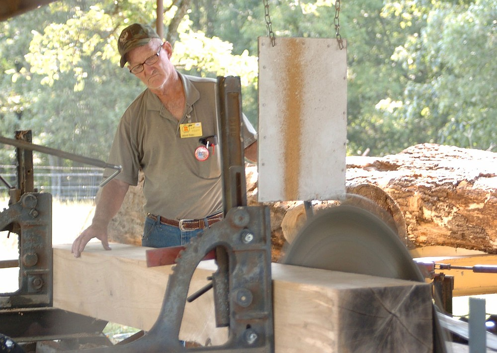 Westside Eagle Observer/RANDY MOLL Harold Bowen, of Huntsville, demonstrates the use of the sawmill at the Tired Iron of the Ozarks fall show on Saturday, Sept. 11, 2021.