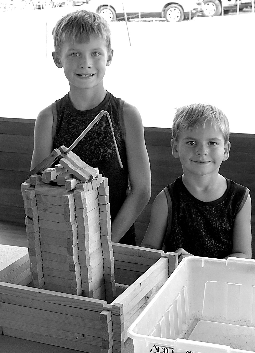 Westside Eagle Observer/ RANDY MOLL Peyton DeCamp, 8, and his brother Anthony, 6, pose next to a building Peyton constructed out of wooden building blocks at the antique home items building on the showgrounds of Tired Iron of the Ozarks on Saturday, Sept. 11, 2021.