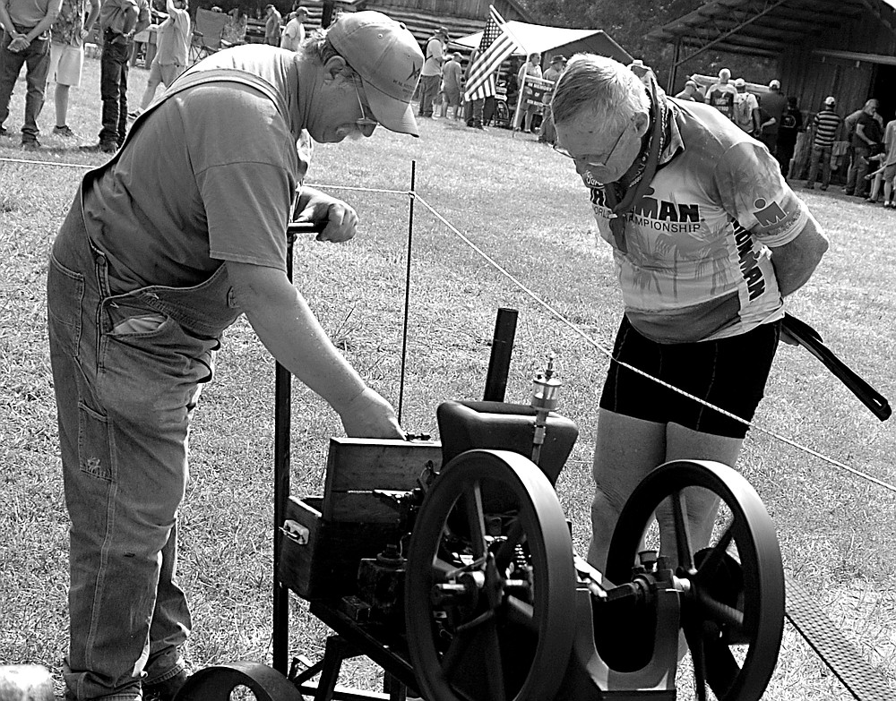 Westside Eagle Observer/RANDY MOLL Steve Montgomery of Nowata, Okla., shows his 1 1/2 horsepower Associated engine to Dennis Moore of Praire Grove at the Tired Iron of the Ozarks fall show in Gentry on Saturday, Sept. 11, 2021.
