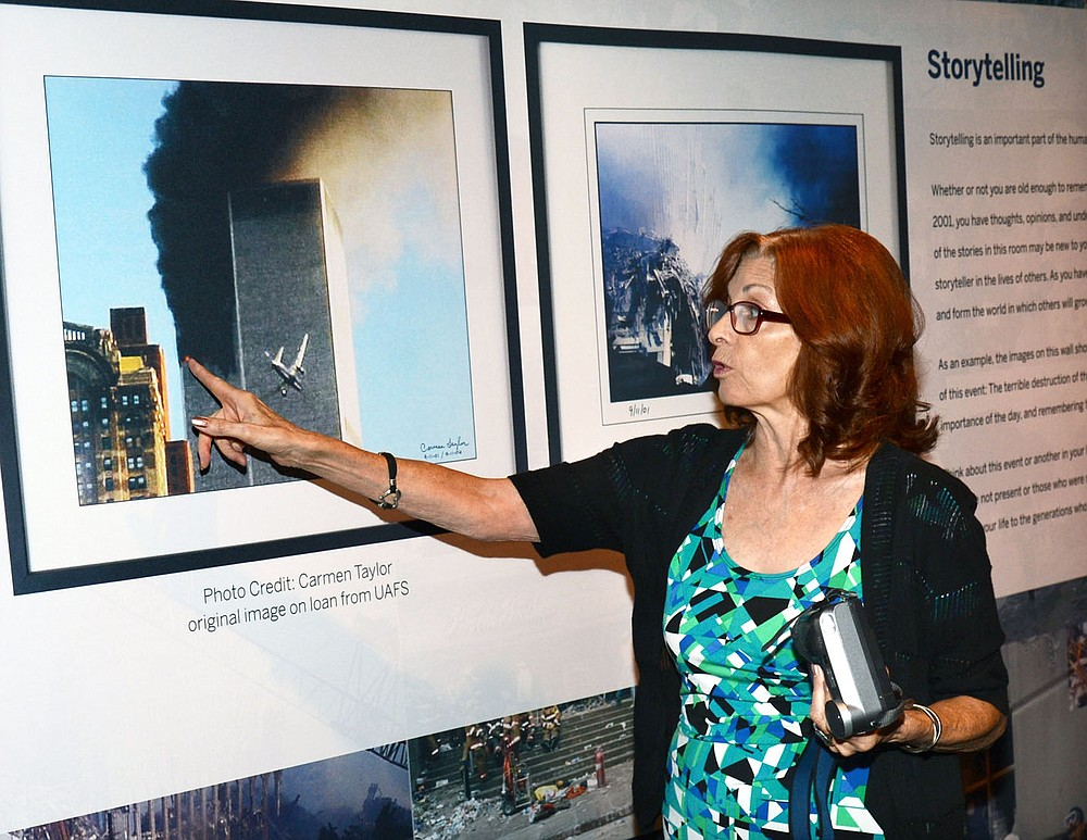 Carmen Taylor of Fort Smith describes what she first saw at the World Trade Center before capturing this image just as the second plane neared the building on Sept. 11, 2001. Taylor was at the U.S. Marshals Museum in Fort Smith where a display of photographs from that day is set up.  (Special to NWA Democrat Gazette/Brian Sanderford)