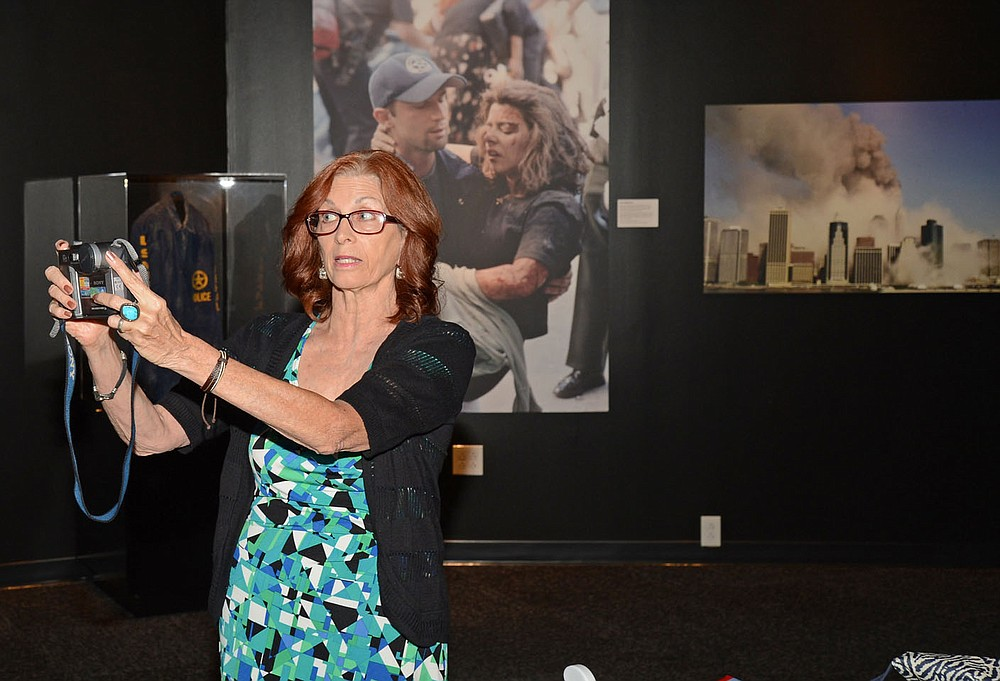 Carmen Taylor of Fort Smith talks about using her Sony Mavica digital camera to capture an image of United Airlines Flight 175 just before it crashed into the World Trade Center South Tower on Sept. 11, 2001. Taylor was at the U.S. Marshals Museum in Fort Smith where display of photographs from that day is set up.  (Special to NWA Democrat Gazette/Brian Sanderford)