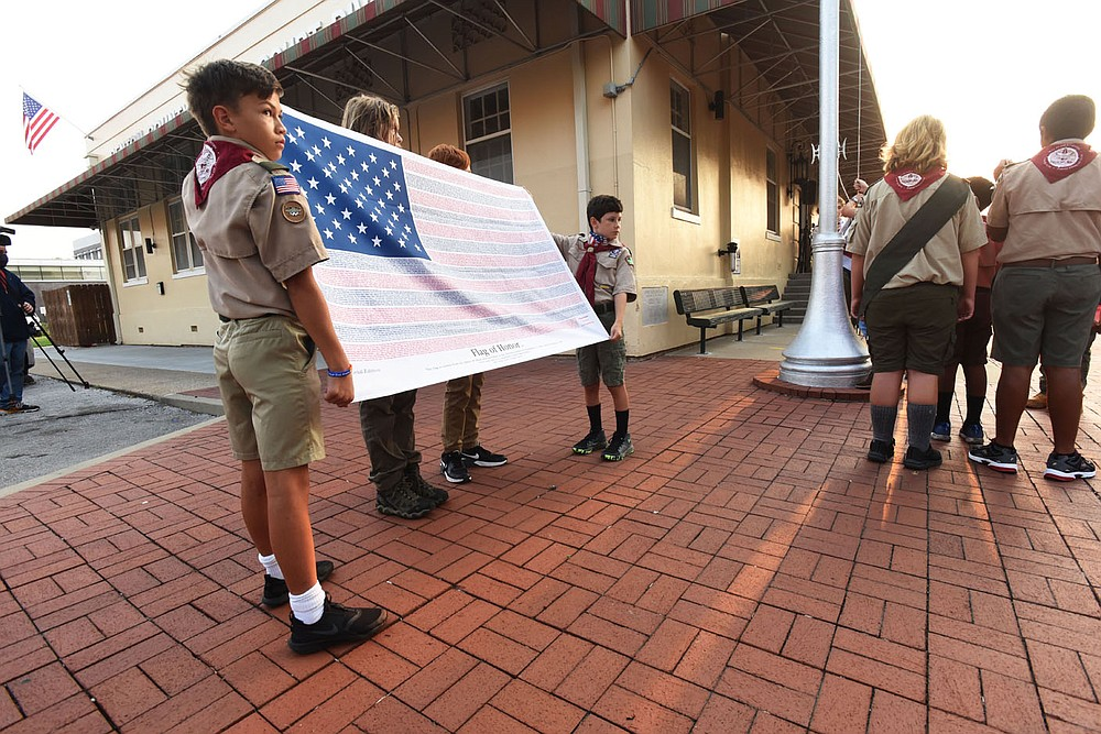 Boy Scouts from Troop 36 in Bentonville Caden Dancer (from left), Benji Wessels (cq), Tristan Browning and Jack Hudson present Saturday Sept. 11 2021 the 9-11 Flag of  Honor during the 9-11 remembrance ceremony on the Bentonville square. Go to nwaonline.com/210912Daily to see more photos. (NWA Democrat-Gazette/Flipi Putthoff)