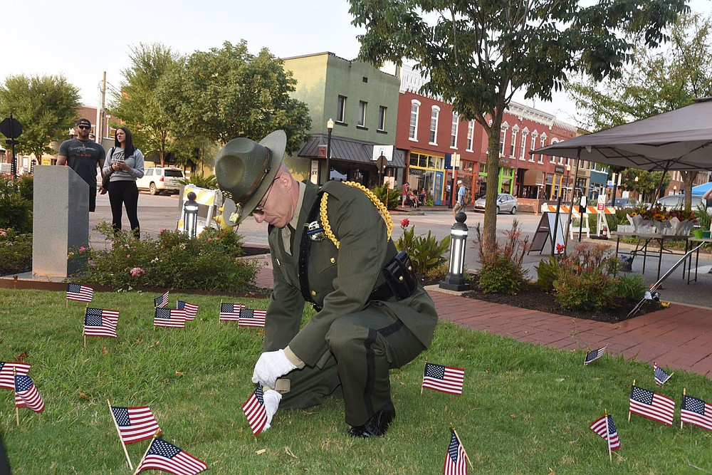 Deputy Michael Dowdle with the Benton County Sheriff's Office Honor Guard on Saturday Sept. 11 2021 places a 9-11 remembrance flag on the courthouse lawn, along with other flags placed by people who attended the 9-11 remembrance ceremony on the Bentonville square. Go to nwaonline.com/210912Daily/ to see more photos. (NWA Democrat-Gazette/Flip Putthoff)