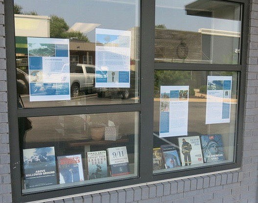 Westside Eagle Observer/SUSAN HOLLAND The front windows at the Gravette Public Library hold a display of posters developed by the 9/11 Memorial and Museum to explain the events of the Sept. 11, 2001, terrorist attack to youngsters who were not yet born at the time of the incident. Also on display are books from the library's collection relating to the attack.