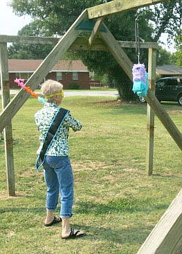 Westside Eagle Observer/SUSAN HOLLAND Zanetta Bedwell swings at a pinata hanging from a framework on the playground at the Church of Christ Saturday afternoon. Bedwell got a few hits in on the target before asking for help from nearby youngsters who knocked it down and released its contents.