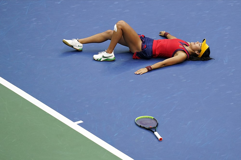 Emma Raducanu, of Britain, lies on the court after defeating Leylah Fernandez, of Canada, during the women's singles final of the US Open tennis championships, Saturday, Sept. 11, 2021, in New York. (AP Photo/Frank Franklin II)