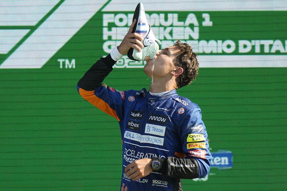 Mclaren driver Lando Norris of Britain drinks champagne from a shoe of Mclaren driver Daniel Ricciardo of Australia who won the Italian Formula One Grand Prix, at Monza racetrack, in Monza, Italy, Sunday, Sept.12, 2021. (AP Photo/Luca Bruno)