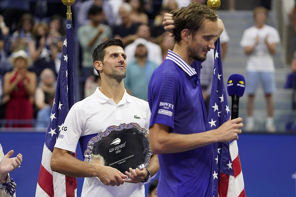 Novak Djokovic, of Serbia, holds the runner-up trophy as Daniil Medvedev, of Russia, prepares to receive the championship trophy after Medvedev defeated Djokovic in the men's singles final of the US Open tennis championships, Sunday, Sept. 12, 2021, in New York. (AP Photo/John Minchillo)